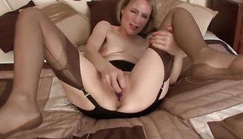 Slim mature solo masturbating on the bed